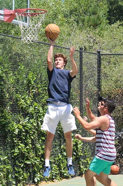 A man making a layup while playing basketball.