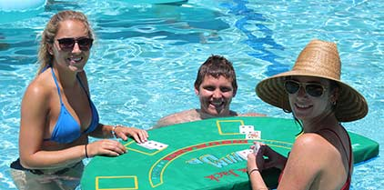 Two women and a child in the pool with women playing cards on a floating table.