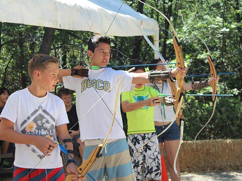 Kids with bow and arrows practicing archery.