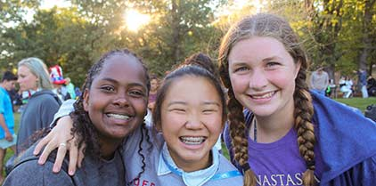Three young girls posing at the camera with smiles on their faces.