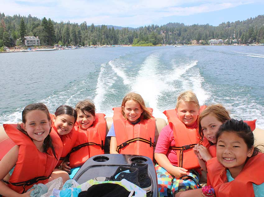 Group of kids in the back of a speed boat on the lake.