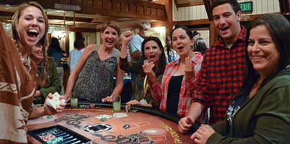 Group around a black-jack table playing and smiling at the camera for a Casino event.