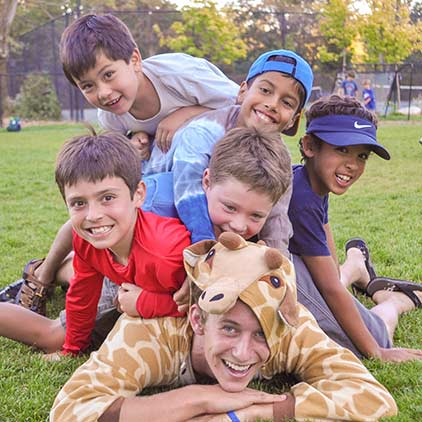 Group of kids and one adult smiling at the camera while laying on the ground on grass.