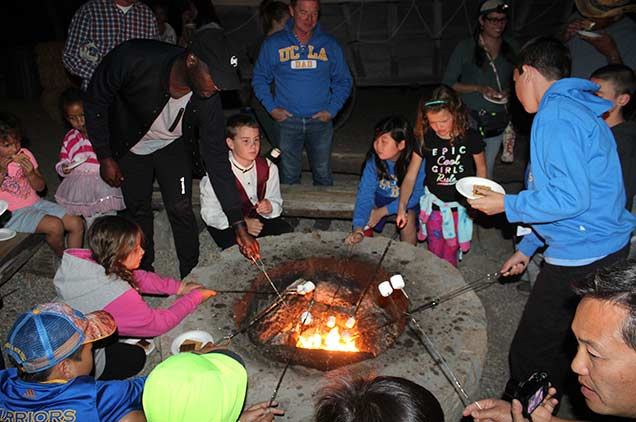 A group of children roasting marshmallows around a campfire.