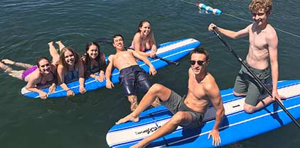 Group of teenagers paddleboarding.