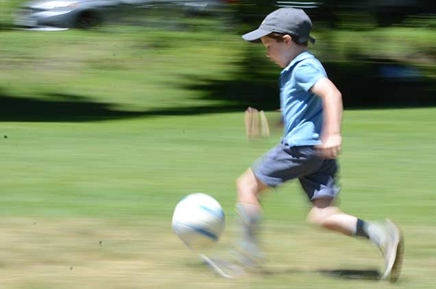 Child dribbling a soccer ball going to score a goal.
