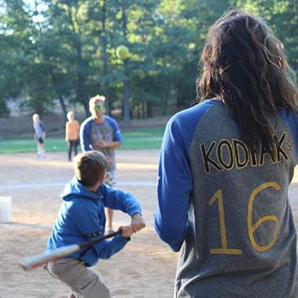 Kid swinging a bat while playing softball.