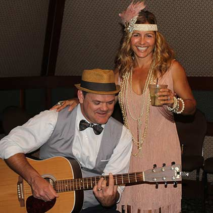 A 1920s event with a man playing guitar and he and the woman next to him dressed as flappers.