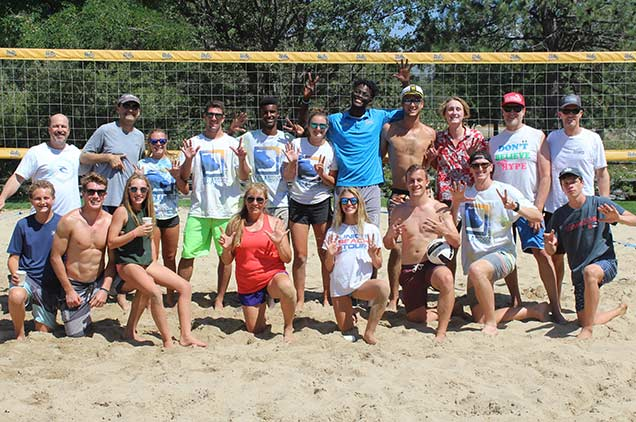A group of visitors posing after playing volleyball.