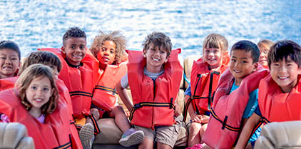 Group of kids with life jackets on a boat.