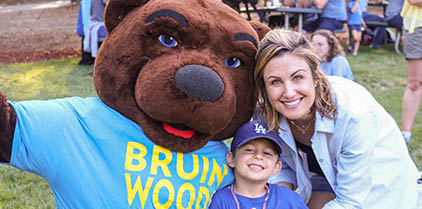 A young boy and her mom posing with Joe Bruin on the lawn.