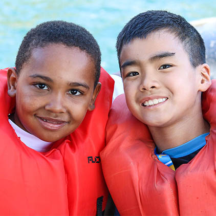 Two boys with life jackets on near the pool.