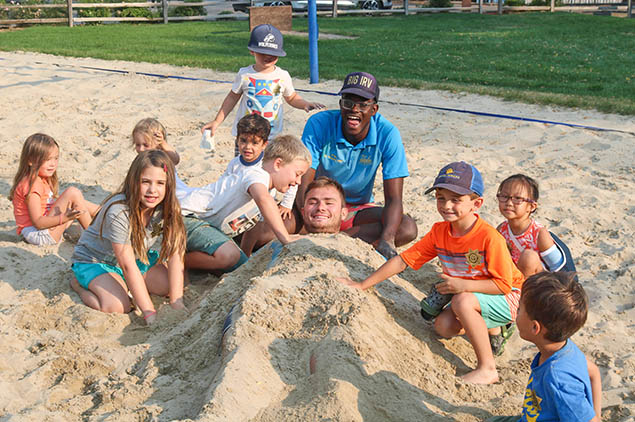 Group of kids playing and building an adult in the sand.