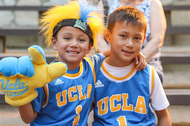 Two kids with UCLA basketball jerseys on posing for the camera sitting on bleachers.