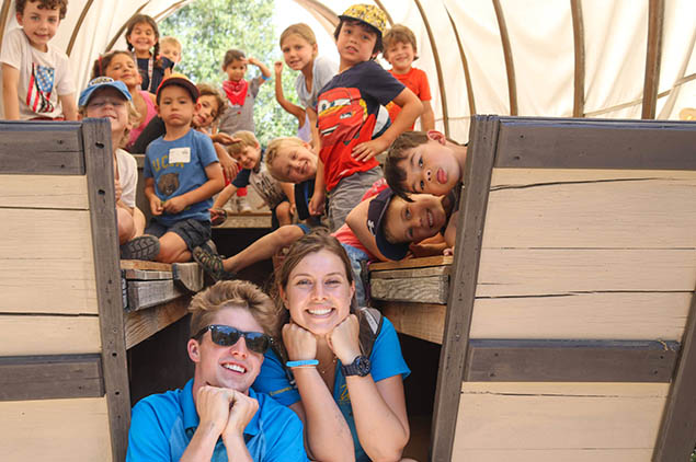 A group of kids smiling at the camera from a pioneer wagon.