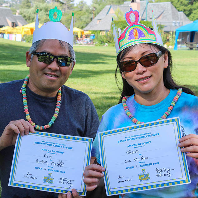 Two guests with paper crowns on posing with certificates having accomplished a feat.