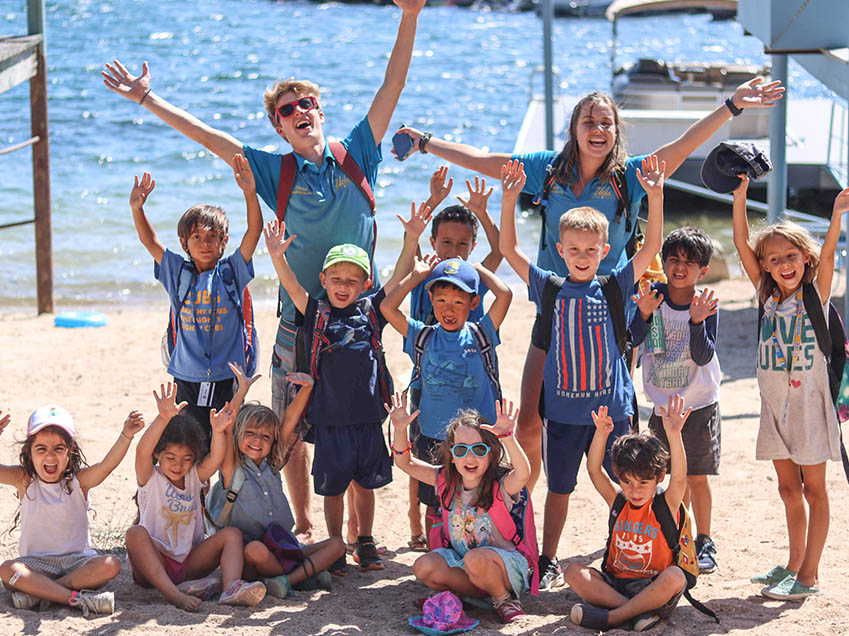Children and two adults with their hands up posing with joy at the camera on the sand of the beach at Lake Arrowhead.