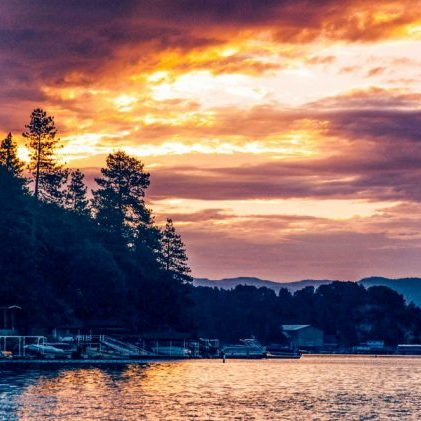 Sunset along the lake with boats and the shoreline with tress in the distance.